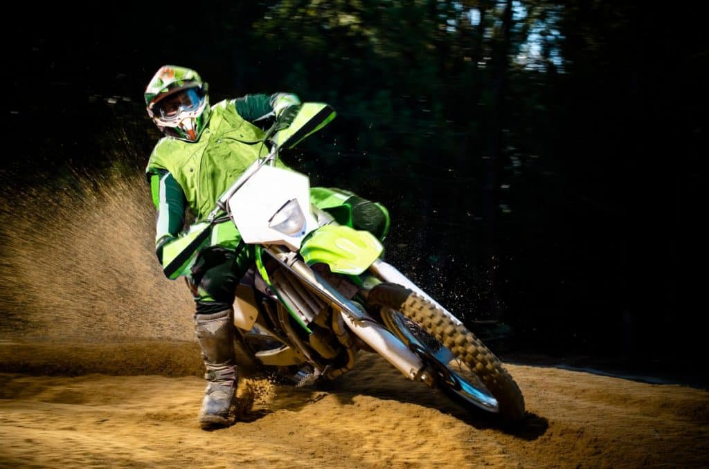 Enduro bike rider on action. Turn on sand terrain