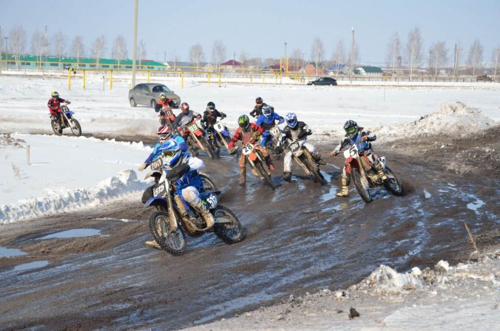 Winter motocross group of riders at the first corner after the start