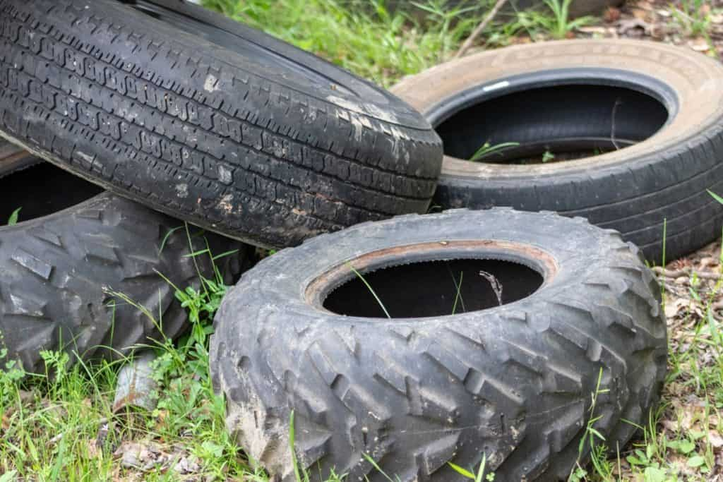 Pile of tires sitting in the grass and weeds