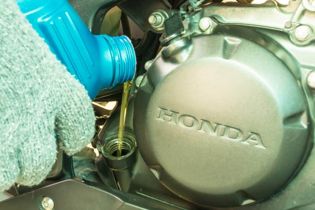 Close up of pouring new oil into honda engine